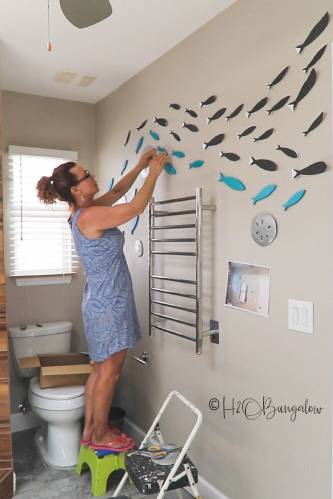 Making a wall mural with wooden fish cutouts