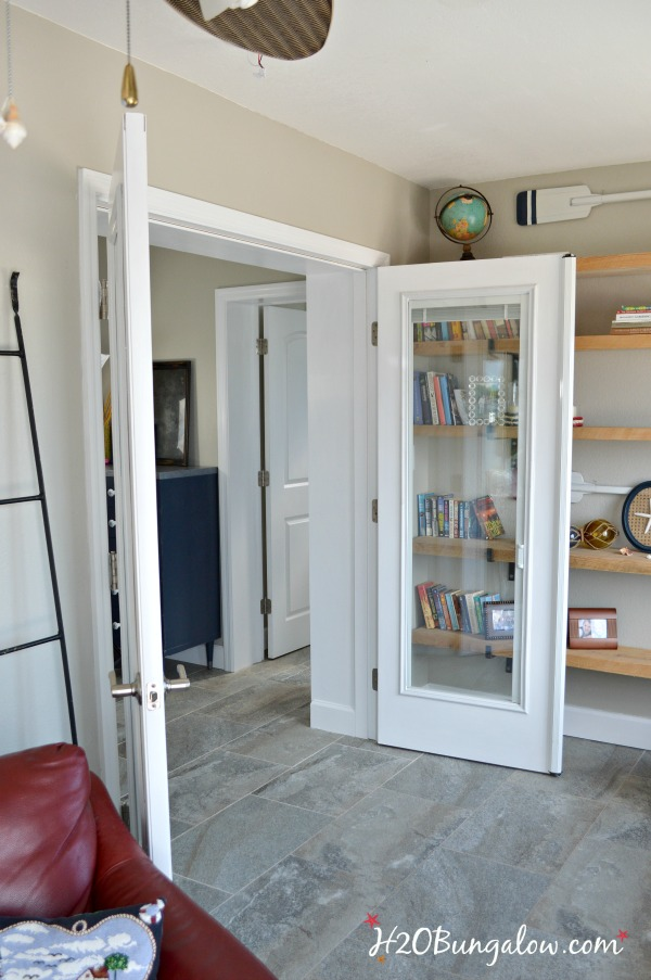 Open white painted french doors with floating bookshelves behind them