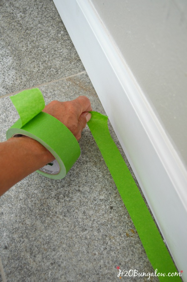 Roll of green painters tape on wrist while putting tape on floor against baseboard