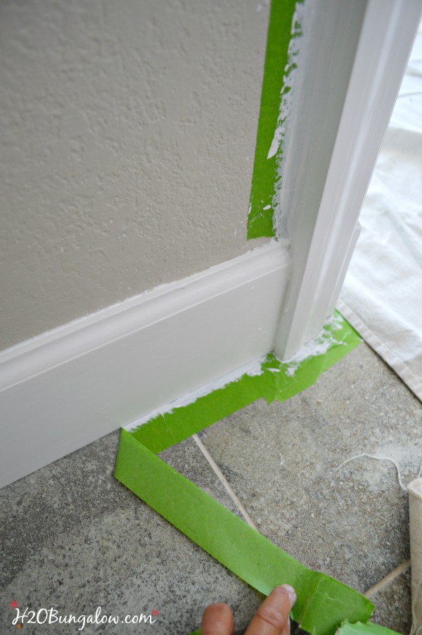 peeling away multi surface painters tape from baseboard