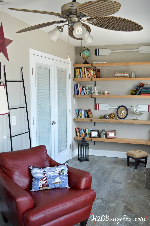white painted french doors floating bookshelves and red chair