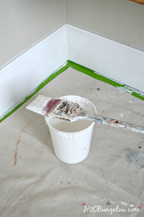 multi surface painters tape with drop cloth, paint container and brush next to baseboard