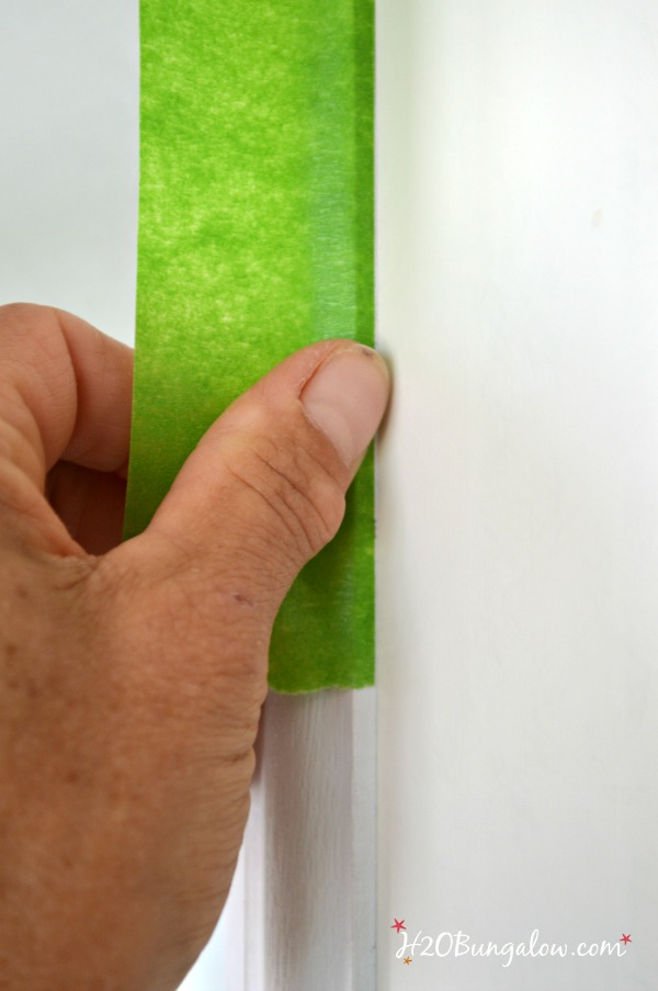 Green frog tape on trim edge with thumb pressing it down
