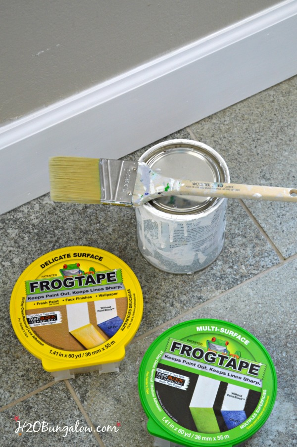 multi surface and delicate frog tape and paint can with brush on top next to baseboard