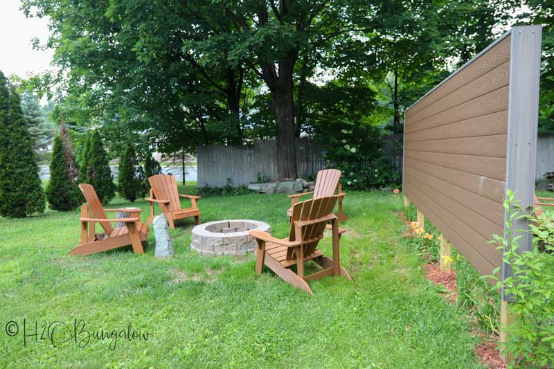 DIY outdoor privacy screen in yard with chairs and fire pit