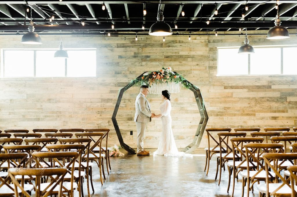 couple standing under DIY moon gate arch