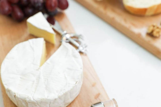cheese, grapes and bread sitting on DIY chesse boards