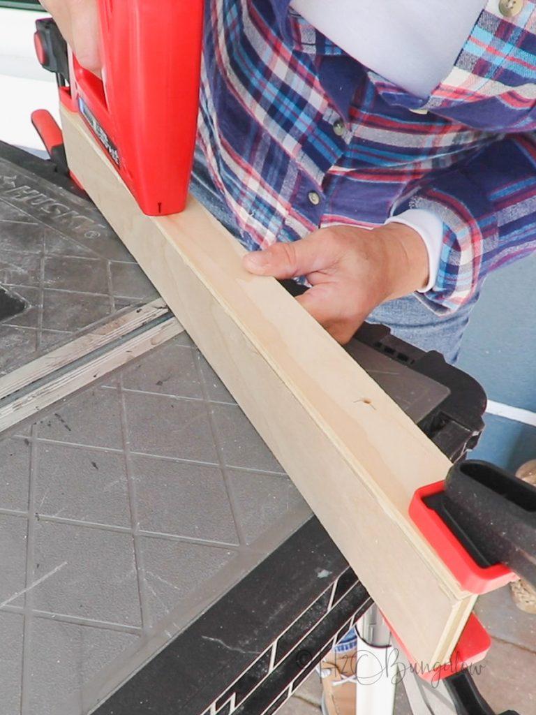 adding brad nails to assemble DIY wood spice rack
