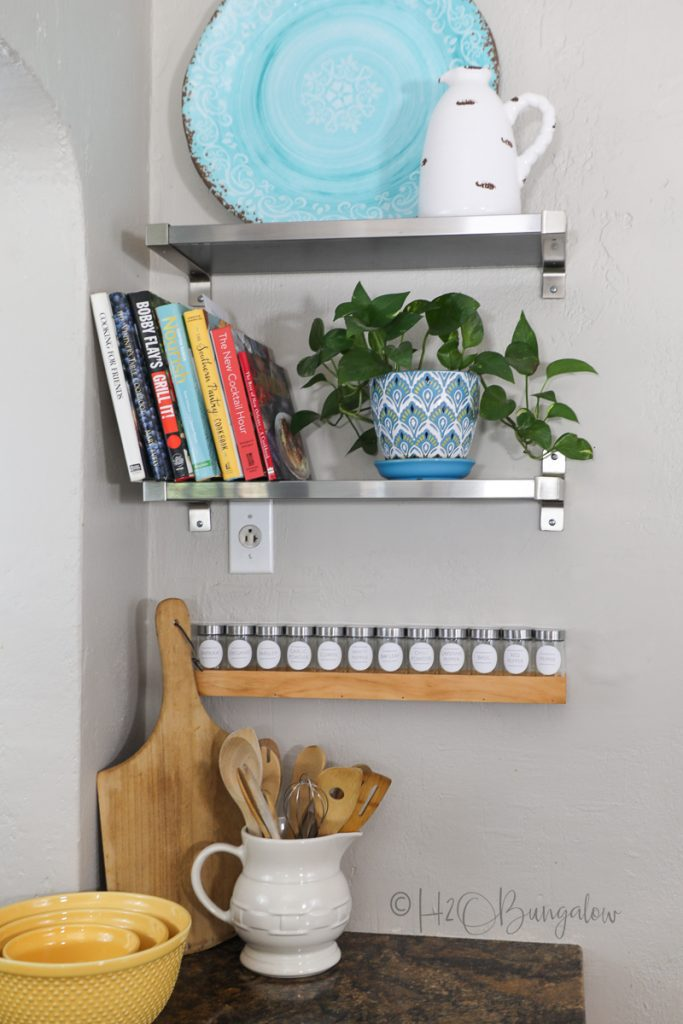 completed DIY wood spice rack with labeled spice jars on wall