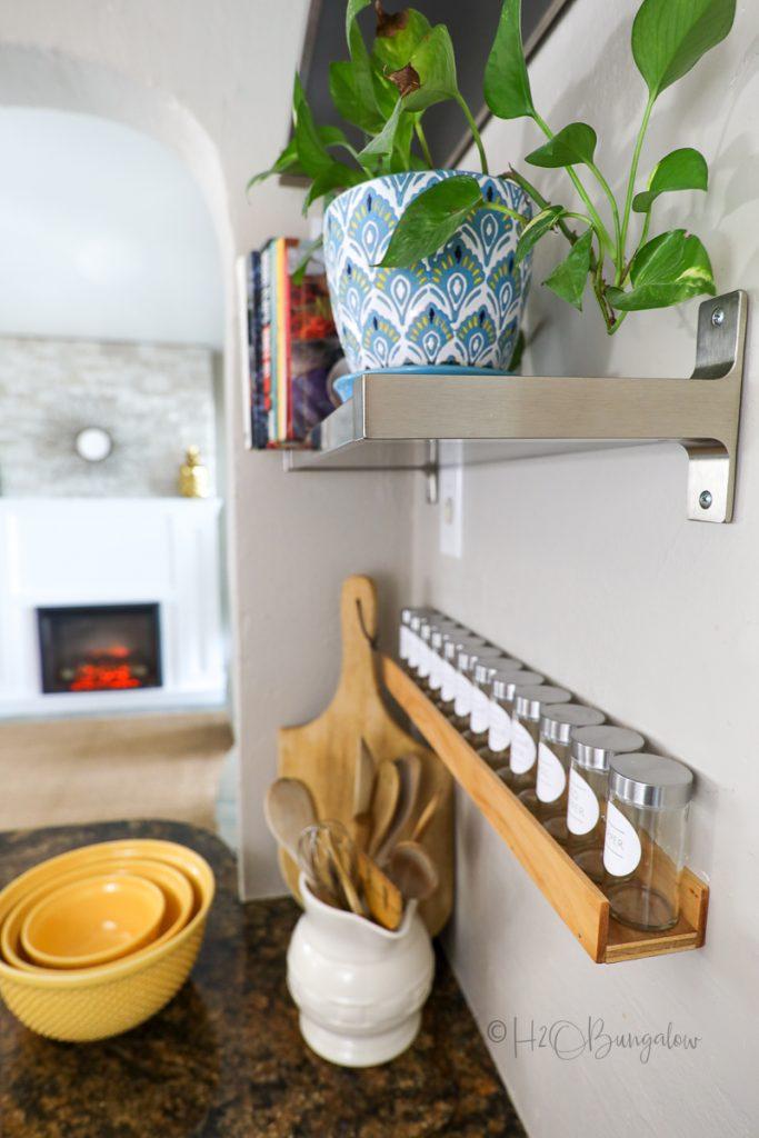 spice jars on handmade spice rack hanging on wall