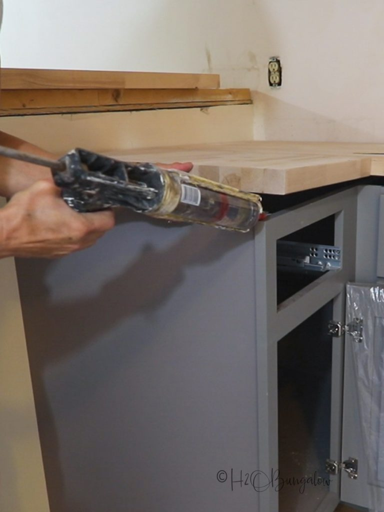 Siliconing under the wood countertop to attach to cabinet base