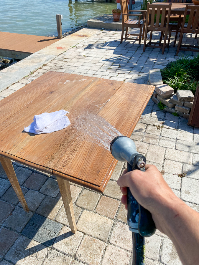 rinsing wood table with a hose to remove bleach residue