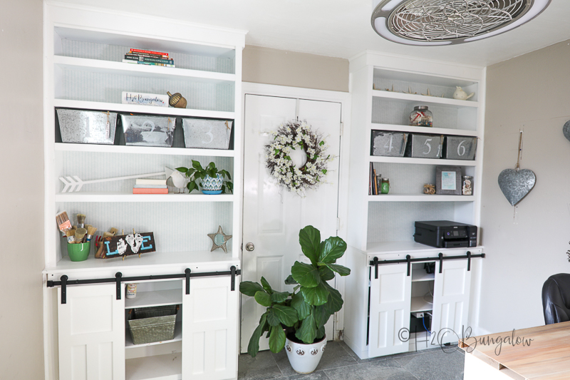 office built in shelves with removable shelf liner decorating back of bookcases