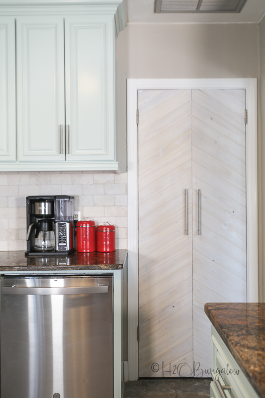 blue painted kitchen cabinets with DIY wood chevron door