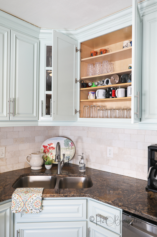 open blue painted cabinet door showing extra shelves for organizing inside
