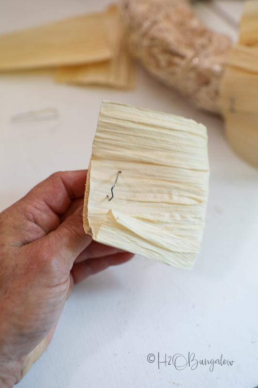 place greening pin into folded corn husk