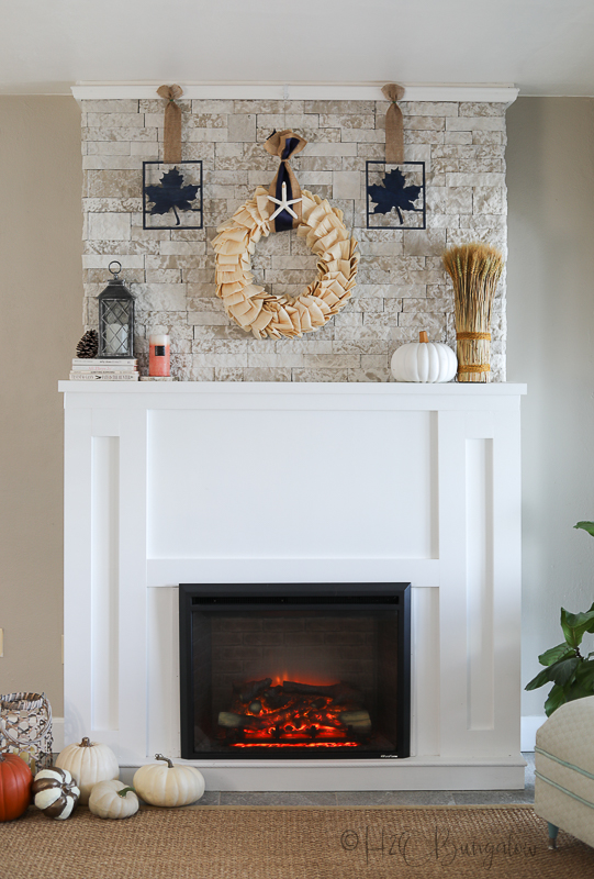 fall themed coastal corn husk wreath on fireplace mantle with blue ribbon
