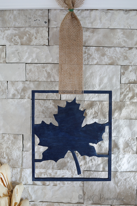 wood maple leaf cut out with burlap next to wreath