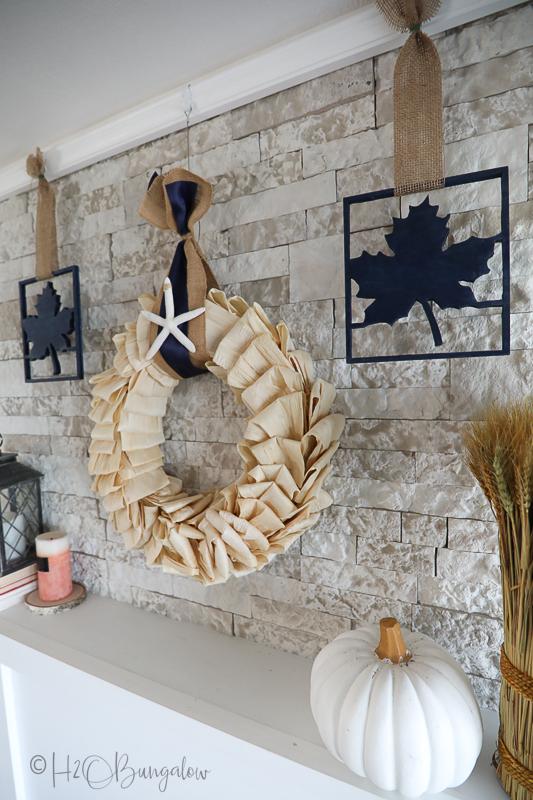 corn husk wreath hanging on stone fireplace mantel